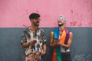 Gay couple laughing and using smartphone in front of a pink and grey wall