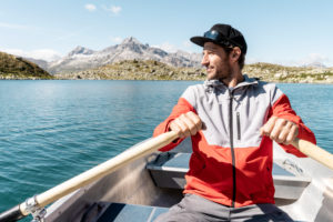 Young smiling man in a rowing boat,Lake Suretta,Graubuenden,Switzerland