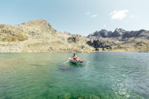 Man in a rowing boat on a crystal clear mountain Lake Suretta,Graubuenden,Switzerland