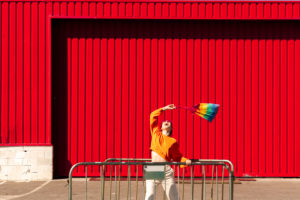 Lesbian with colorful bag and a barrier in front of a red wall