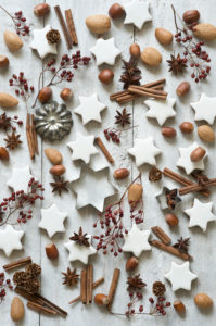 Star shaped cookies,cinnamon sticks,star anise,cookie cutters,pine cones,rose hips,almonds and hazelnuts