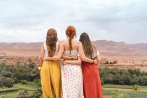 Back view of three young women standing arm in arm looking at the city,Ouarzazate,Morocco