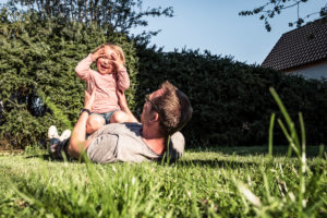 Father playing with little daughter in the garden