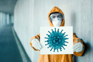 Portrait of man wearing protective clothing holding sign with a depiction of a virus