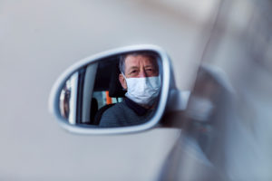 Reflection of senior man wearing mask in wing mirror of a car