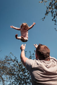 Father throwing little daughter up in air