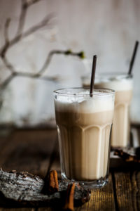 Glass of iced†chai†with frothy milk and cinnamon