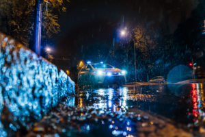 Spain, Madrid, Surface view of police car driving in middle of rainy night