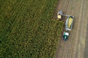 Germany, Bavaria, Drone view of combine and tractor harvesting corn
