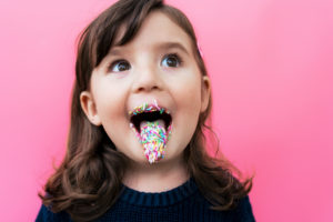 Portrait of happy little girl with sugar granules on lips and tongue in front of  pink background