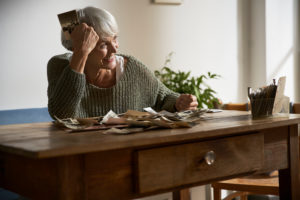 Happy senior woman sitting at table at home watching old photos