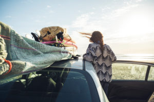 Back view of woman with car on the beach looking to the sea, Tafedna, Morocco