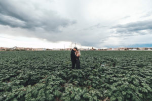 Young couple with transparent umbrella standing in a field hugging each other, Alboraya, Spain