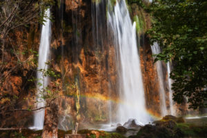 Croatia, Small rainbow over splashing waterfall in Plitvice Lakes National Park