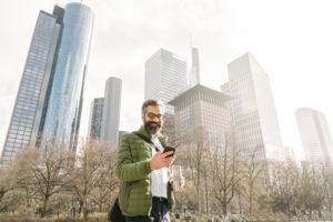 Man using smartphone in front of skycrapers, Frankfurt, Germany