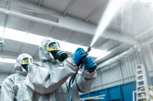 Low angle view of sanitation workers spraying chemical from hose in warehouse