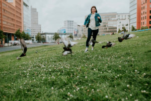 Germany, Berlin, Young woman running on grass surprising flock of pigeons