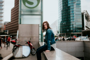 Germany, Berlin, Portrait of young woman sitting on†underpass wall
