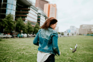 Germany, Berlin, Rear view of young woman wearing denim jacket