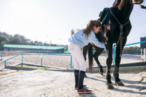 Young girl putting equipment while preparing horse to ride on training ground