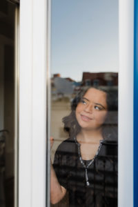 Thoughtful woman with down syndrome smiling while looking through window