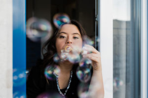 Young woman with down syndrome blowing bubbles from window at home