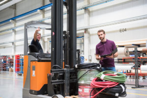 Warehouseman and worker on forklift in warehouse