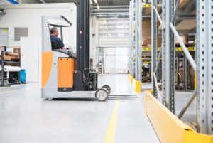 Worker on forklift in high rack warehouse
