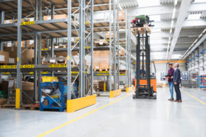Two men and worker on forklift in high rack warehouse