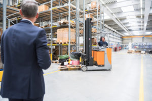 Businessman and worker with forklift in high rack warehouse