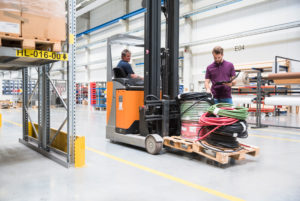 Warehouseman and worker on forklift in high rack warehouse
