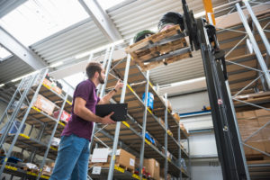 Warehouseman and goods on forklift in high rack warehouse