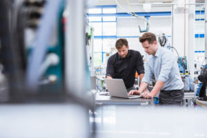 Two men using laptop in factory