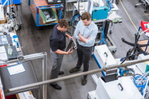 Two men having a meeting in factory examining product