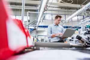 Man using laptop in factory
