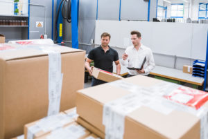 Two men with parcel and clipboard in storehouse of a factory