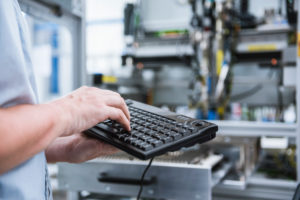 Close-up of man using keyboard in factory