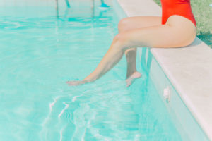 Legs of woman wearing red swimsuit sitting at the poolside