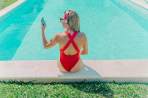 Woman wearing red swimsuit sitting at the poolside with headphones and smartphone