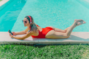 Woman wearing red swimsuit lying at the poolside with headphones and smartphone