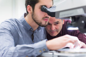 Man looking through microscope in a factory