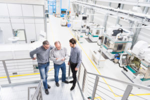 Three businessmen having a discussion in a factory