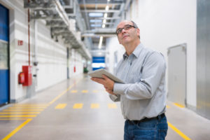 Businessman holding tablet on corridor in a factory
