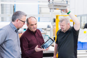 Three men with tablet having a discussion in a factory