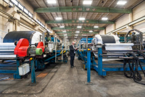 Senior businessman in a rubber processing factory