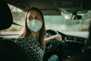 Mid adult woman with protective mask in car