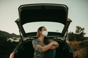 Mid adult woman with protective mask sitting at boot and looking sideways