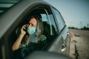 Mid adult woman with protective mask using smartphone in car