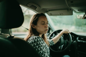 Mid adult woman breething deeply in car