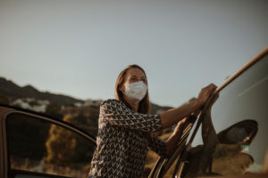 Mid adult woman with protective mask at car